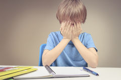 Child made his homework at home. The boy fed up and covers his face with hands. Stock Photos