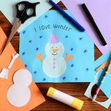 Child made a paper card with a snowman, snowflakes and words I love winter. Scissors, glue stick, pencil, markers, colored paper Stock Photos