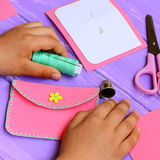 Child made a simple felt purse. Handicraft supplies on a wooden table. Fun and easy teaching kids to hand sew. Kids sewing concept Stock Photography