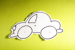CHILD MADE SKETCH, little car draw black on white. SKETCH made by a child, little car drawed on a cut out white piece of paper shot on a bright green Stock Image
