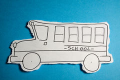 CHILD MADE SKETCH, School bus draw black on white. SKETCH made by a child, little School bus draw on a cut out white piece of paper shot on a bright Cyan blue Stock Photo