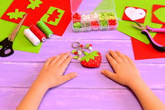 Child made a strawberry keychain of felt and beads. Child shows keychain crafts. Kids hands on a wooden table. Handicraft material. Handicraft materials and royalty free stock photography