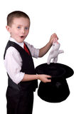 Child Magician. Child dressed as a magician pulling a rabbit from his hat isolated over a white background Royalty Free Stock Photo