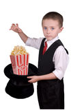 Child Magician. Child dressed as a magician with hat full of popcorn isolated over a white background Royalty Free Stock Image