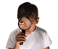 Child with Magnifying Glass. Young Latino boy looking through a magnifying glass on white background Royalty Free Stock Photo