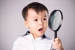 Child with magnifying glass Stock Images