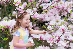 Child with magnolia flower. Little girl with flowers Stock Photos