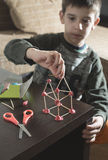 Child make house. With wooden sticks and plasticine Stock Photo