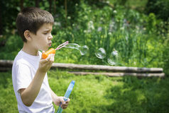 Child makes bubbles Stock Photography