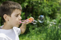 Child makes bubbles Royalty Free Stock Photo