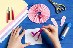 Child makes bunnies for Easter decoration. Step 7. Child makes bunnies out of paper for Easter decoration. Creative idea for children`s party. DIY concept. Step royalty free stock photography