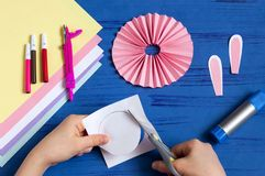 Child makes bunnies for Easter decoration. Step 8. Child makes bunnies out of paper for Easter decoration. Creative idea for children`s party. DIY concept. Step royalty free stock images
