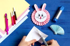 Child makes bunnies for Easter decoration. Step 13. Child makes bunnies out of paper for Easter decoration. Creative idea for children`s party. DIY concept. Step stock photo