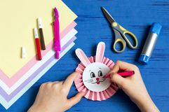 Child makes bunnies for Easter decoration. Step 10. Child makes bunnies out of paper for Easter decoration. Creative idea for children`s party. DIY concept. Step royalty free stock photography