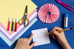 Child makes bunnies for Easter decoration. Step 4. Child makes bunnies out of paper for Easter decoration. Creative idea for children`s party. DIY concept. Step stock images