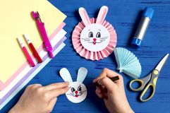 Child makes bunnies for Easter decoration. Step 14. Child makes bunnies out of paper for Easter decoration. Creative idea for children`s party. DIY concept. Step royalty free stock photography