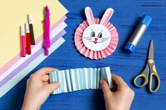 Child makes bunnies for Easter decoration. Step 11. Child makes bunnies out of paper for Easter decoration. Creative idea for children`s party. DIY concept. Step stock photos