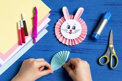 Child makes bunnies for Easter decoration. Step 12. Child makes bunnies out of paper for Easter decoration. Creative idea for children`s party. DIY concept. Step royalty free stock images