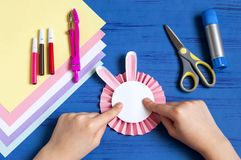 Child makes bunnies for Easter decoration. Step 9. Child makes bunnies out of paper for Easter decoration. Creative idea for children`s party. DIY concept. Step stock photo