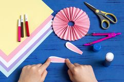 Child makes bunnies for Easter decoration. Step 6. Child makes bunnies out of paper for Easter decoration. Creative idea for children`s party. DIY concept. Step stock photo