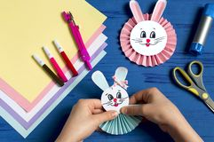 Child makes bunnies for Easter decoration. Step 15. Child makes bunnies out of paper for Easter decoration. Creative idea for children`s party. DIY concept. Step stock images