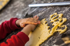 Child makes cookies. Hands of a small child making Christmas cookies out of buttered dough Stock Photography