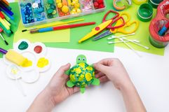 The child makes a craft toy from foam plastic tortoise. Material for creativity and education stock photo