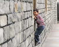 Child makes faces. While climbing on a stone wall Stock Photo