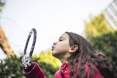 Child makes giant soap bubbles. 7 year old girl in outdoor in the garden in winter makes big soap bubbles Stock Photography