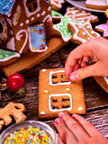 Child makes gingerbread house for Christmas. Royalty Free Stock Photography