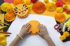The child makes a hand-made paper. Tiger origami. Royalty Free Stock Images