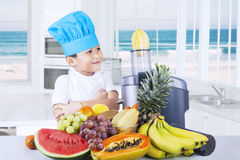 Child makes healthy fruits juice Royalty Free Stock Image