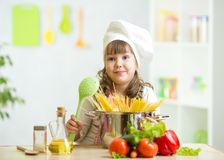 Child makes healthy vegetables meal in the kitchen. Child girl makes healthy vegetables meal in the kitchen Royalty Free Stock Images