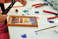 The child makes a panel of colored glass mosaic. Tools for creativity. stock photo