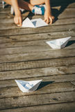 Child makes a paper boats sitting on wooden pier Royalty Free Stock Photography