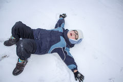 Child makes a snow angel Stock Images