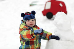 Child makes a snowman Royalty Free Stock Images