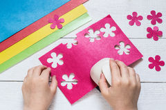 The child makes special hole punch flowers of paper Royalty Free Stock Photos