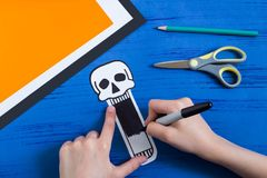 Child makes toothy paper toys for Halloween. Step 5. Child makes toothy paper toys skull and Jack-o`-lantern for Halloween. Children`s art project. DIY concept Royalty Free Stock Photo