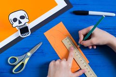 Child makes toothy paper toys for Halloween. Step 7. Child makes toothy paper toys skull and Jack-o`-lantern for Halloween. Children`s art project. DIY concept Stock Image