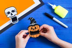 Child makes toothy paper toys for Halloween. Step 12. Child makes toothy paper toys skull and Jack-o`-lantern for Halloween. Children`s art project. DIY concept Stock Photography