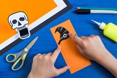Child makes toothy paper toys for Halloween. Step 10. Child makes toothy paper toys skull and Jack-o`-lantern for Halloween. Children`s art project. DIY concept Stock Images