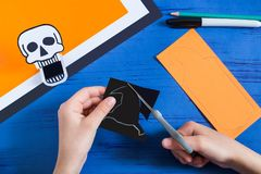 Child makes toothy paper toys for Halloween. Step 8. Child makes toothy paper toys skull and Jack-o`-lantern for Halloween. Children`s art project. DIY concept Stock Photography
