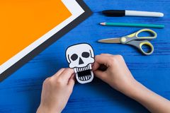 Child makes toothy paper toys for Halloween. Step 6. Child makes toothy paper toys skull and Jack-o`-lantern for Halloween. Children`s art project. DIY concept Stock Image