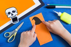 Child makes toothy paper toys for Halloween. Step 9. Child makes toothy paper toys skull and Jack-o`-lantern for Halloween. Children`s art project. DIY concept Stock Images