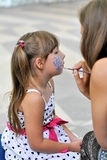 Child with makeup. Wizard girl draws paint makeup Royalty Free Stock Photography