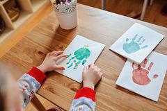 Child making christmas handprints post cards at home Royalty Free Stock Photos