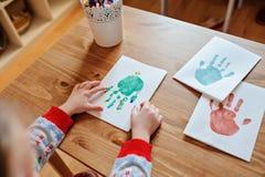 Child making christmas handprints post cards at home. Child sitting and making christmas handprints post cards at home royalty free stock photos