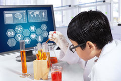 Child making experiments in the lab. Little boy using chemical and beaker to make experiments in the laboratory Royalty Free Stock Image