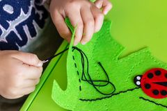 Child Making Felt Soft Toy Of Green Leaf And Red Ladybag . Child DIY Activity. Close-up. Children Handicraft Concept Royalty Free Stock Photo